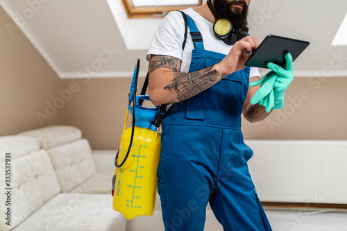 Photo Exterminator in work wear writing annotation about pest extermination plan