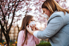 Mother Placing Protective Mask On Face Of Her Daughter. Coronavirus, Covid-19 Concept.