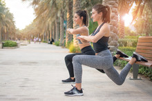 Two Beautiful Young Sporty Women Doing Lunge Step On A Bench Outdoors. Fitness Friends Exercising In The Park