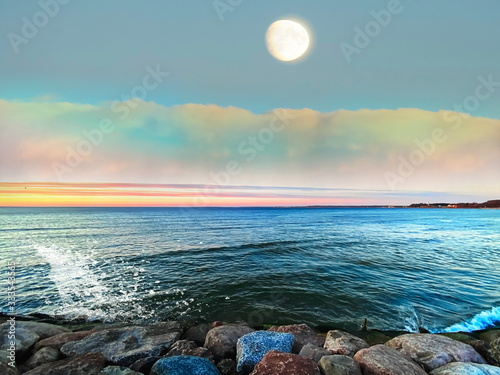 sunset and moon on sea  ,pink blue clouds on horizon ,emerald green sea wave water splash on stones  ,nature landscape tropical island