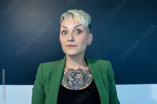 ragazza bionda tatuata con giacca verde con faccia buffa, isolata su sfondo grig Canvas Print