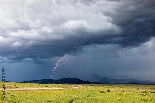 Fototapeta Thunderstorm lightning strike with rain and dark storm clouds