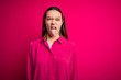 Leinwandbild Motiv Young beautiful brunette girl wearing casual shirt standing over isolated pink background sticking tongue out happy with funny expression. Emotion concept.