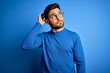 Leinwandbild Motiv Young handsome man with beard wearing casual sweater and glasses over blue background confuse and wondering about question. Uncertain with doubt, thinking with hand on head. Pensive concept.