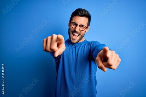 Canvastavla Young handsome man with beard wearing casual sweater and glasses over blue backg