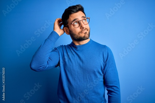 Young handsome man with beard wearing casual sweater and glasses over blue background confuse and wondering about question Fototapet