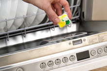 Putting Tab Into Full Dishwasher Close Up. Integrated Dishwasher Machine Full Loaded. Woman Hand Holding Dishwasher Detergent Tablet.