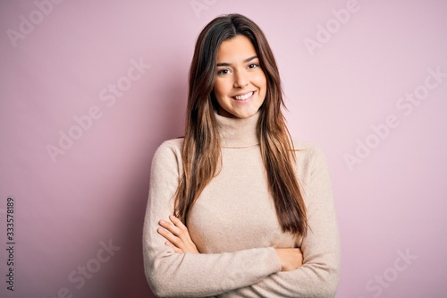 Fototapety, obrazy: Young beautiful girl wearing casual turtleneck sweater standing over isolated pink background happy face smiling with crossed arms looking at the camera. Positive person.