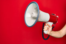Beautiful Hand Of Man Holding Megaphone Over Isolated Red Background