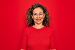 Middle age senior brunette woman wearing casual t-shirt standing over red background with a happy and cool smile on face. Lucky person.