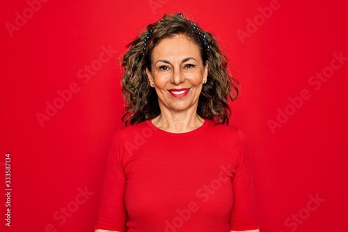 Fototapeta Middle age senior brunette woman wearing casual t-shirt standing over red background with a happy and cool smile on face. Lucky person. obraz