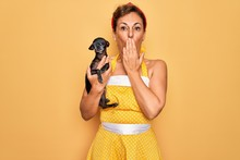 Middle Age Senior Pin Up Woman Wearing 50s Style Retro Dress Holding Chihuahua Dog Cover Mouth With Hand Shocked With Shame For Mistake, Expression Of Fear, Scared In Silence, Secret Concept