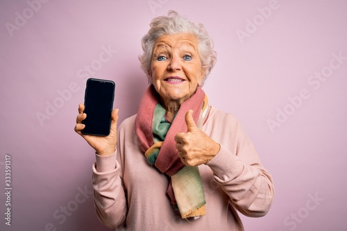 Cuadros en Lienzo Senior beautiful grey-haired woman holding smartphone showing screen over pink b