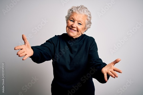 Senior beautiful woman wearing casual black sweater standing over isolated white background looking at the camera smiling with open arms for hug Fototapet