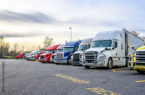 Fotografiet Different big rigs semi trucks with semi trailers standing in row on truck stop