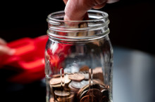 Two Fingers Holding Coins To Be Dropped Into A Glass Jar