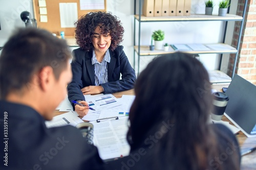 Fototapeta Young beautiful couple applying for mortgage. Sitting smiling happy meeting with real state agent signing mortgage loan at bank obraz