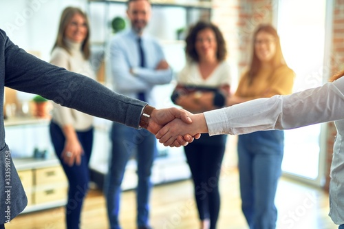 Group of business workers standing together shaking hands at the office Wallpaper Mural