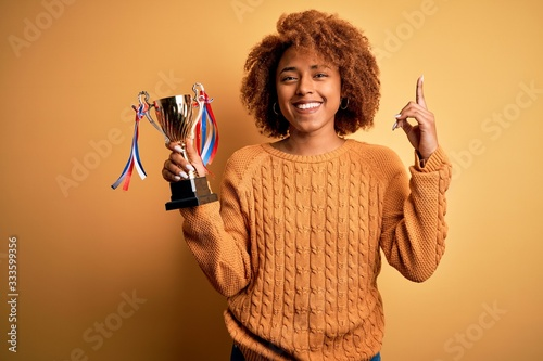 Photo Young African American afro woman with curly hair holding winner champion trophy