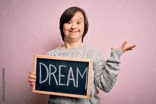 Obraz na plátně Young down syndrome woman holding blackboard with dream word as message of happi