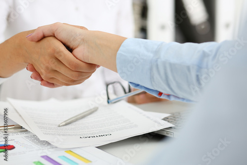 Partnership agreement closeup with woman in suit shake hand as hello in background Canvas Print