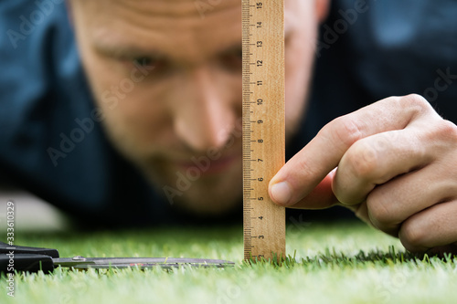 Man Using Measuring Scale While Cutting Grass Canvas Print