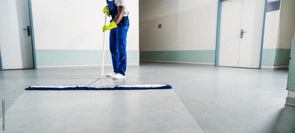 Fototapeta Male Janitor Cleaning Floor In Office