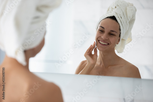 Young attractive woman with towel on head looking in mirror while cleanses skin Tapéta, Fotótapéta