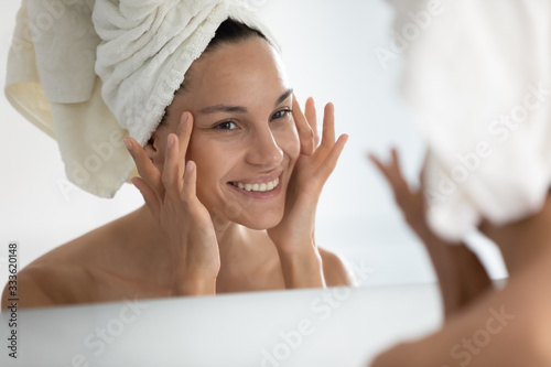 Foto After beauty home spa procedure woman looks at perfect skin in mirror touch face feels satisfied