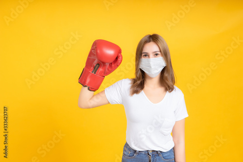 Young asian woman with medical mask protection coronavirus COVID-19 fighting wearing boxing gloves healthy and safety care concept on yellow background isolated studio shot, copy space Poster Mural XXL