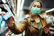 Leinwandbild Motiv Woman wearing protective mask while using cell phone and buying food in grocery store during virus epidemic.