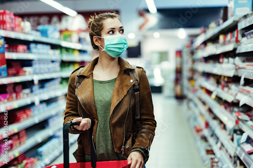 Fotografía Woman wearing face mask while shopping in supermarket during virus pandemic
