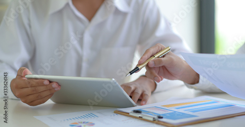 Photo Stock market experts use tablet to follow the news to assess the volatile stock market situation