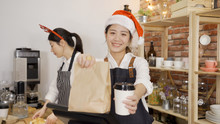 Smiling Young Asian Barista In Santa Hat Giving Disposable Coffee Cups And Paper Bag To Camera. Colleague In Reindeer On Head Prepare Order In Counter. Attractive Girls Staff Working On Xmas Eve.