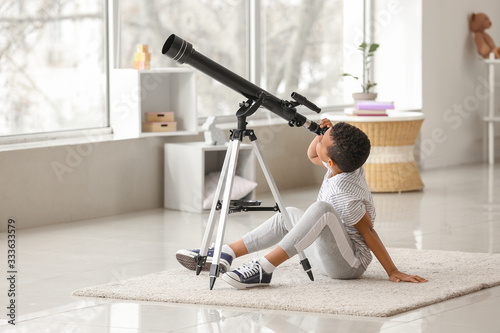 Fotomural Little African-American boy with telescope at home