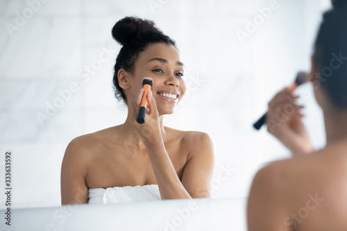 Photo Beautiful african 35s woman after shower holds soft brush applying foundation on face, enjoy daily morning routine, preparing for dating, working day look at mirror