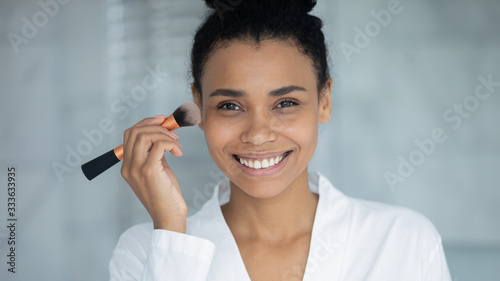 African 30s ethnicity woman in bathrobe holds make up brush apply foundation con Canvas Print
