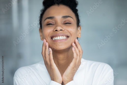 Fotografie, Obraz Beautiful african woman touch face enjoy ideal flawless fresh smooth facial skin close up portrait