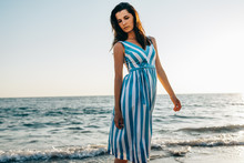 Pretty Model Woman Walking Along The Beach And The Sea Sunset Background. Brunette Female Wearing Striped Dress Has Dreamy Expression Against Ocean Background. Travel Concept.