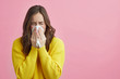 Leinwanddruck Bild - Pretty girl is Sneezing into a tissue because of her allergy or cold