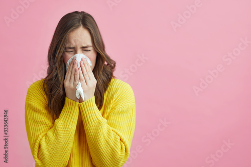 Canvas Print Pretty girl is Sneezing into a tissue because of her allergy or cold