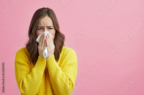 Beautiful girl having allergy and is using a tissue while having a nice bright s Wallpaper Mural