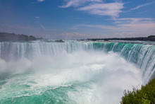 Panoramic View Over The Impressive Niagara Falls From The Hornblower Cruise Boat On The Middle Of The Niagara River. On The Border Between US And Canada. Massive Water Falls Under The Cloudy Sky.