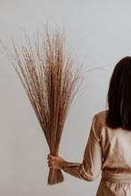 Female Holding A Bunch Of Dried Straw In Her Left Hand In A Studio With White Wall