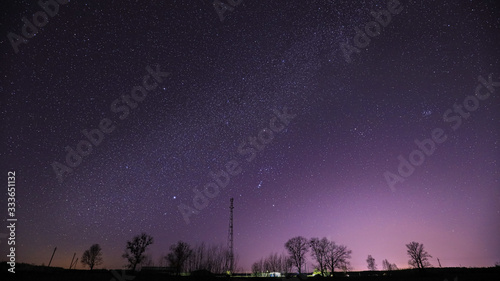 Fototapeta Real Night Sky Stars Above Landscape With Telecommunications Cell Phone Tower Or With Antenna. Natural Starry Sky With Milky Way Galaxy Above Rural Countryside Landscape In Belarus obraz