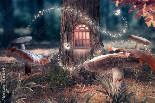 Fototapeta premium Fantazja zaczarowany bajkowy las z gigantycznymi grzybami, magicznym domem elfa lub krasnala z lśniącym oknem w dziupli sosny i latającymi bajkowymi magicznymi motylami opuszczającymi ścieżkę ze świetlistymi iskierkami