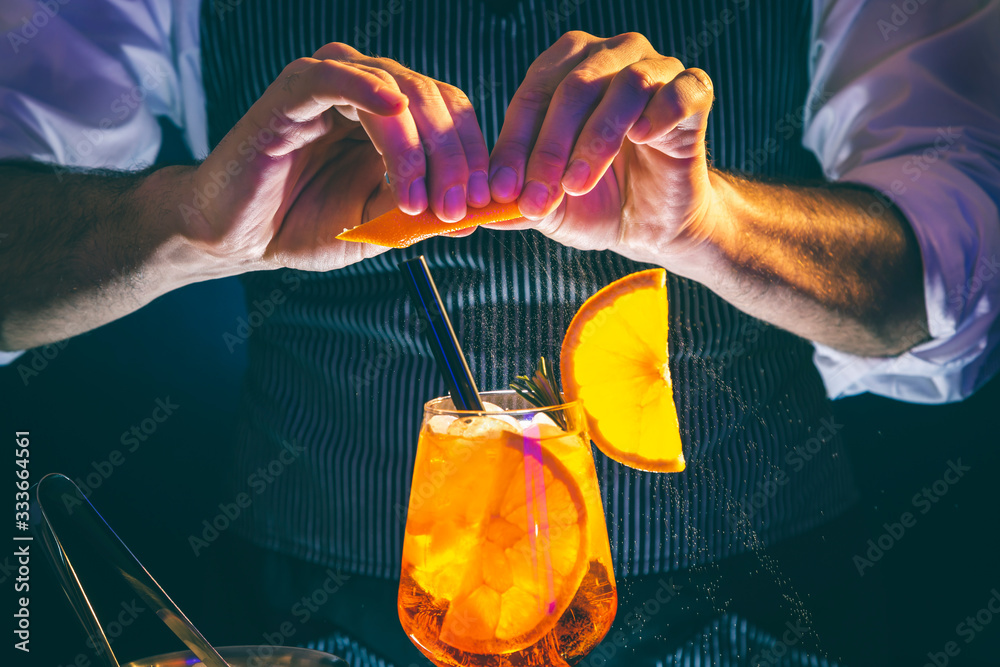Fototapeta Bartender sprinkling Aperol spritz cocktail glass with orange juice