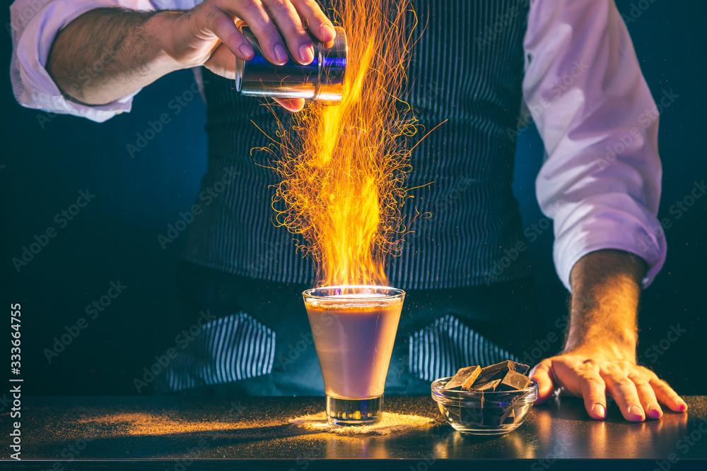 Fototapeta Bartender making a cocktail on fire