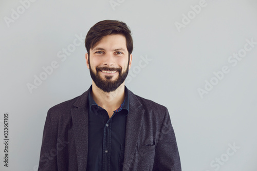 Obraz Positive bearded guy in a jacket smiling looks at the camera on a gray background. - fototapety do salonu