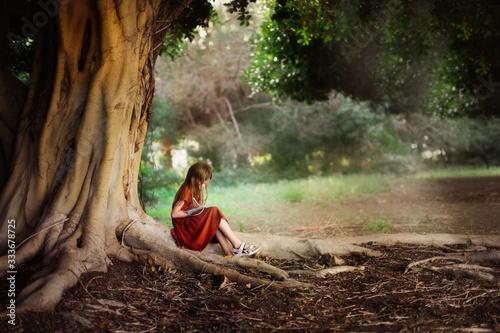 Fototapeta Child writes in notebook under large green tree obraz